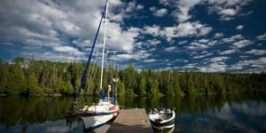 photo of a sailboat on a lake with calm water, blue skies and trees spanning the background.