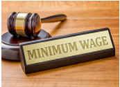 minimum wage engraved on desk plaque with gavel behind